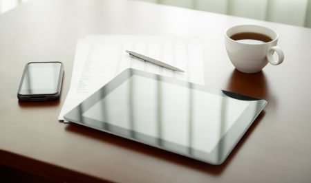 workplace: Modern workplace with digital tablet and mobile phone, cup of tea, pen and paper with numbers. Stock Photo
