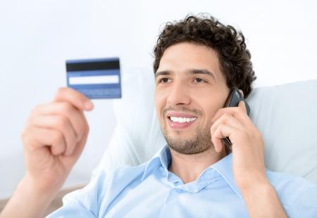 calling: Hombre joven guapo busca en la tarjeta de cr�dito y hablar por tel�fono m�vil moderno Studio disparo