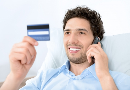 card payment: Young handsome man looking on credit card and talking on modern mobile phone  Studio shot