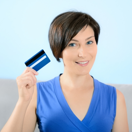 tarjeta de credito: Mujer bonita joven con la sonrisa en la cara que muestra la tarjeta de cr�dito