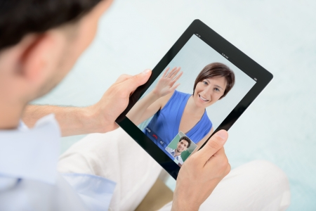 A young couple talking to each other via online video chat  photo