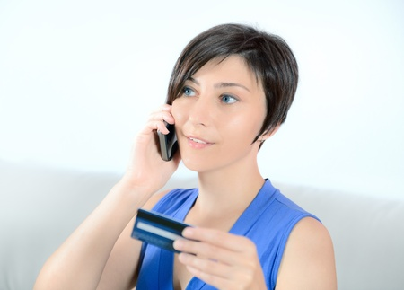 Young woman calling on mobile phone and holding a credit card  photo