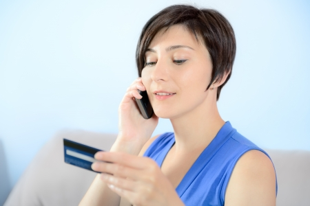 Young woman calling on mobile phone and holding a credit card