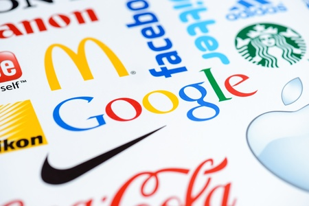 known: Kiev, Ukraine - June 27, 2012 -  Close up photo of the Google logo on the printed paper together with a collection of well-known brands of the world.