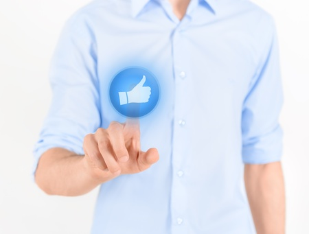 Man touching social media button with thumb up symbol on a virtual screen  Isolated on white Stock Photo - 15064923