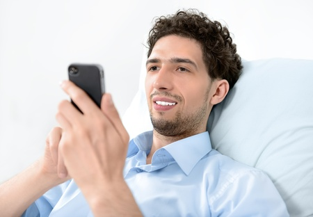 25 35: Young handsome man using modern mobile smart phone  Studio shot  Stock Photo