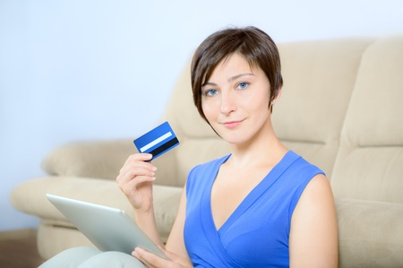 25 35: Young woman sitting with digital tablet and holding a credit card