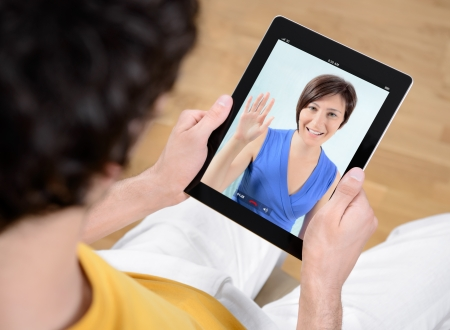 Man and woman communicate through video chat on modern digital tablet  photo