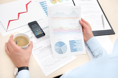 Businessman at the workplace drink coffee and looking some papers with charts and numbers Stock Photo - 16248328