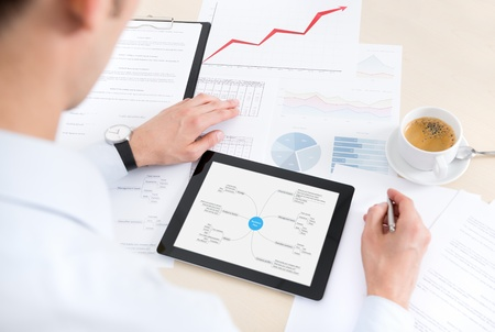 mindmap: Businessman at the workplace working with documents and using modern digital tablet  Stock Photo