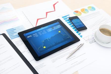 desarrollo econ�mico: Lugar de trabajo de negocios moderna con los datos del mercado de valores en una tableta digital, banca m�vil en un smartphone y muchos cuadros y gr�ficos en una computadora de escritorio