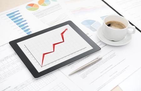 informe comercial: Escritorio con informe el �xito del negocio en una tableta digital moderna, algunos papeles con tablas y gr�ficos y con una taza de caf� Foto de archivo