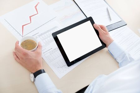 Businessman at workplace drinking coffee and looking at the blank digital computer Stock Photo - 16555411