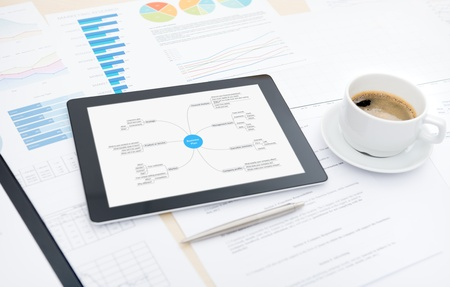 place of research: Modern digital tablet with business plan on screen, cup of coffee and some papers and documents with charts and numbers on a desktop in office