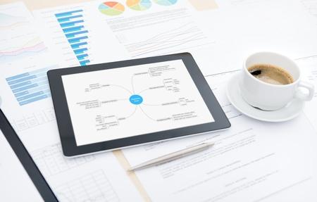 Moderne tablette numérique au plan d'affaires à l'écran, tasse de café et quelques papiers et documents avec des graphiques et des chiffres sur un ordinateur de bureau dans le bureau