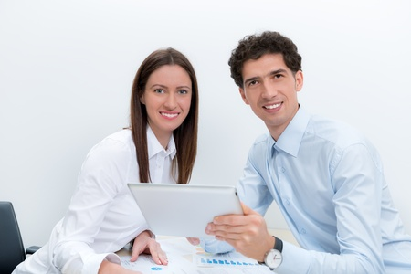 co workers: Businessman and businesswoman at the workplace planning with digital tablet