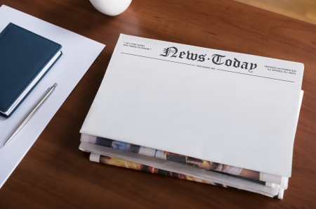 breaking news: A stack of newspapers with headline  News Today  and blank space for information lying on the office desktop  Stock Photo
