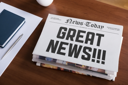 Newspaper with hot topic  Great news  lying on office desk