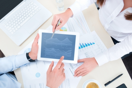 contabilidad: Hombre de negocios y empresaria analizar el informe financiero en una tableta digital moderna. Vista superior tiro.