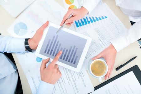 La gente d'affari discutere e analizzare informazioni di mercato i dati su un computer moderno tavoletta digitale. Vista photoshoot superiore. Archivio Fotografico