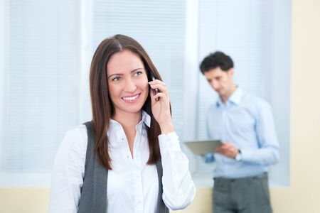 Beautiful young business woman speaks on a mobile phone. Young businessman with digital tablet on the background in soft focus. Stock Photo - 17158141