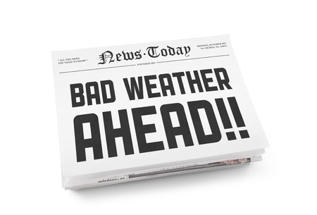 A stack of newspapers with headline Bad Weather Ahead. Isolated on white. photo