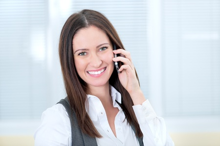 speaks: Beautiful smiling business lady speaks on a mobile phone.