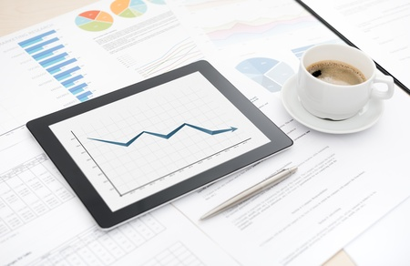 bankrupt: Desktop with bad statistic report on a modern digital tablet, some papers with charts and graphs and with a cup of coffee  Stock Photo
