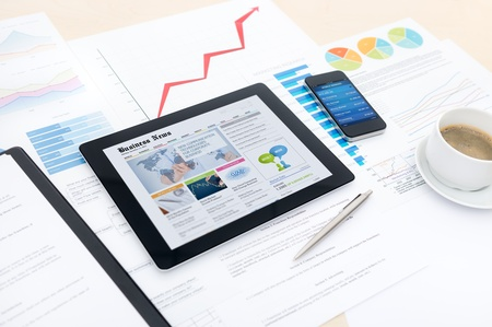 Modern business workplace with business news website on a digital tablet, mobile banking on a smartphone and some charts and graphs on a desktop Stock Photo - 17413585