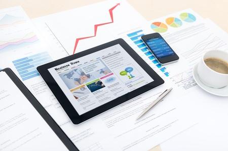 website: Moderne Business-Arbeitsplatz mit Wirtschaftsnachrichten Website auf einem digitalen Tablette, Mobile Banking auf einem Smartphone und einige Diagramme und Grafiken auf einem Desktop