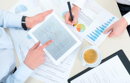 ビジネスを所得のチャートと現代のデジタル タブレットを持つグラフを分析するチーム。トップ ビュー写真撮影。