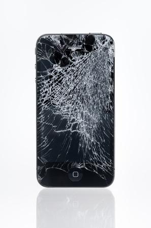 developed: Kiev, Ucrania - 25 de enero de 2013: El viejo iPhone 4 de Apple con pantalla estrell�, tiro del estudio. 4 Apple iPhone desarrollado por Apple inc. en junio de 2010.