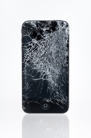 Kiev, Ukraine - January 25, 2013: The old Apple iPhone 4 with crashed screen, studio shot. Apple iPhone 4 developed by Apple inc. in June, 2010.  Stock Photo - 18115511