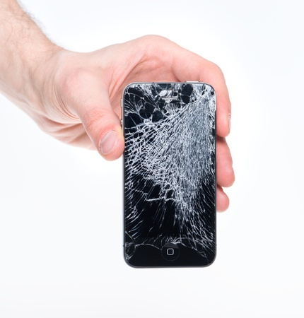 Kiev, Ukraine - January 25, 2013: Hand holding Apple iPhone 4 with broken screen, studio shot. Apple iPhone 4 developed by Apple inc. in June, 2010.