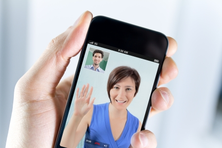 Closeup of a male hand holding a smartphone during a video call with his girl field photo