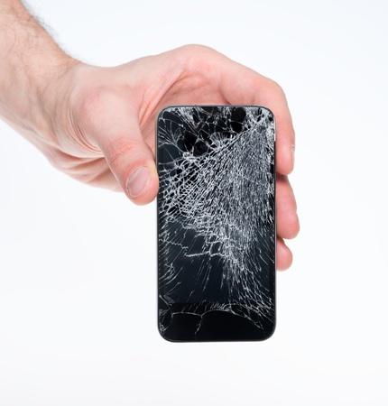 Studio close-up van een mannelijke hand, houden van een smartphone met een gebarsten scherm, geïsoleerd op een witte achtergrond