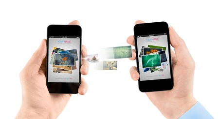 sharing: Two hands holding mobile smartphones while transferring pictures from one to another