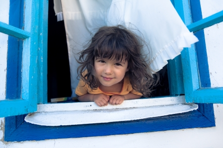 Smiling girl looking from a blue window with white curtains  photo