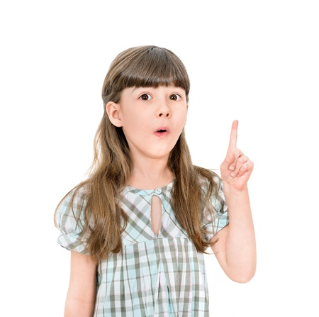 smart girl: Clever little girl with a bright idea pointing upwards with her finger to gain attention  Isolated on white with blank copyspace above her finger
