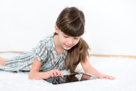 Ni�a jugando con una tableta digital moderna mientras que miente en una alfombra blanca en una habitaci�n blanca photo