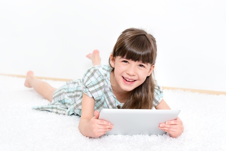 kids learning: Joyful pretty little girl laughing as she lies on her stomach on a white carpet playing with a modern digital tablet in a white room