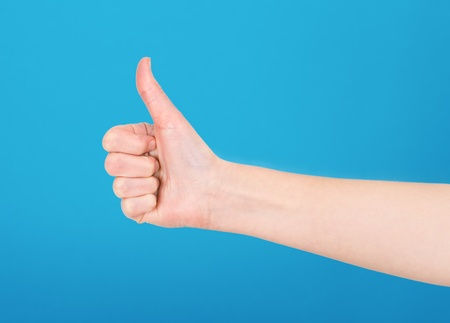 Right hand showing thumb up on blue background Stock Photo - 18463456