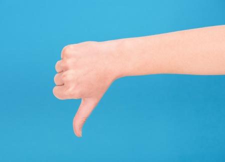 mano derecha: La mano derecha que muestra el pulgar hacia abajo sobre fondo azul Foto de archivo