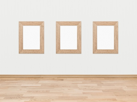Three empty rectangular wooden frames displayed on a white wall above a hardwood wooden floor  photo