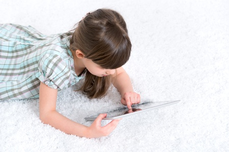 media gadget: Young girl  6-7 year  looking and playing with digital tablet in a white room