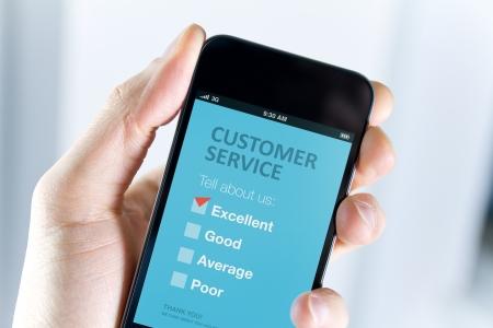 servicio al cliente: Men s de la mano que sostiene el tel�fono m�vil moderno con el formulario de encuesta de servicio al cliente en una marca roja en pantalla excelente opci�n muestra la satisfacci�n del cliente Foto de archivo