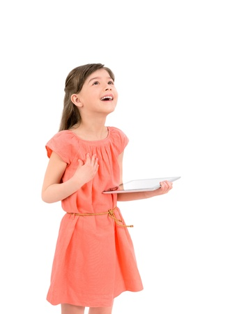 looks: Inspired happy young girl looking up on copyspace and holding in her hand digital tablet  Isolated on white background