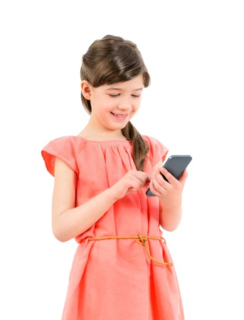 Smiling little cute girl in red dress playing on mobile smartphone  Isolated on white background  photo