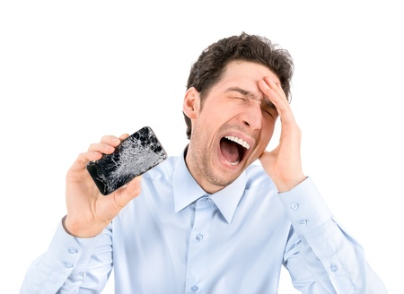 fail: Handsome angry businessman showing broken smartphone with crashed screen  Isolated on white background