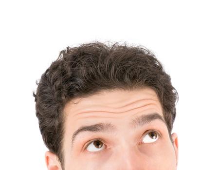 cara sorpresa: Retrato de un hombre joven y guapo mirando hacia arriba aislados en fondo blanco Foto de archivo